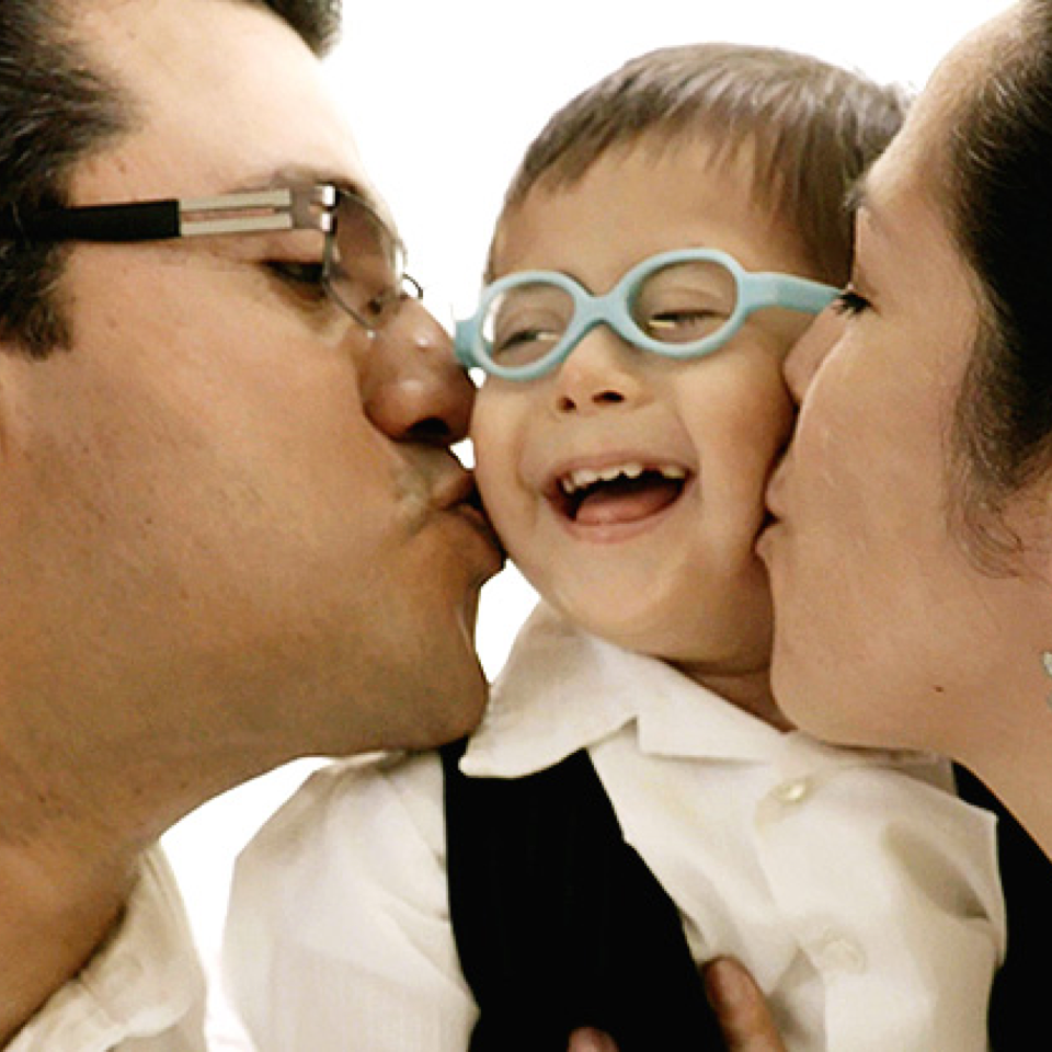 An RMHC family, the Acostas, with parents kissing their smiling child in glasses