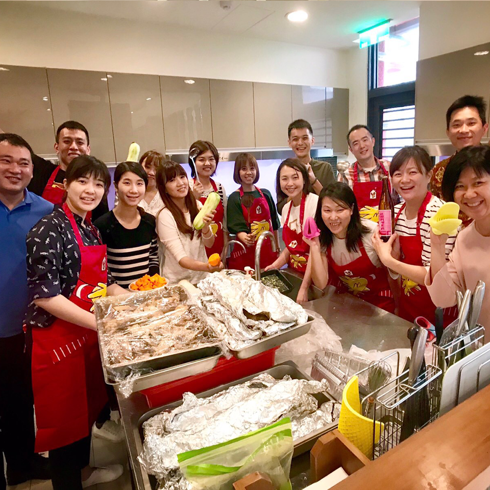 Colleagues from an RMHC corporate partner who donated their time posing around food prepared at their local Ronald McDonald House program
