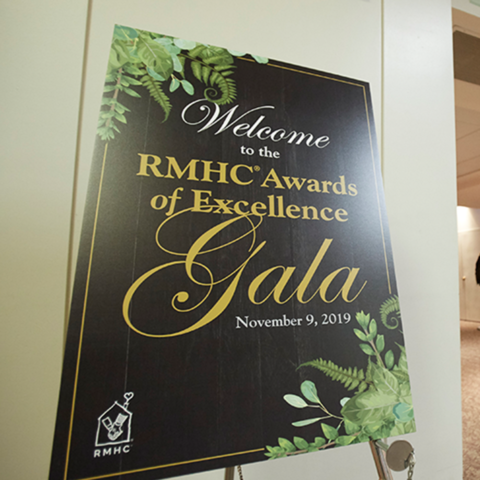 "A gala poster, reads, ""Welcome to the RMHC Awards of Excellence Gala, November 19, 2019"""