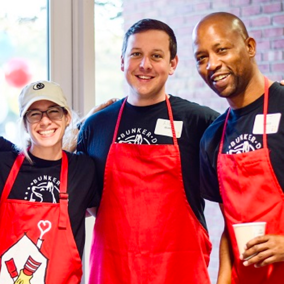 Three volunteers in red RMHC aprons, posing during service at a House program