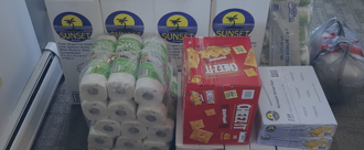 Shaded background image, stack of paper products and boxed food