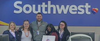 Shaded background image, five people from Southwest Airlines standing in front of the Southwest sign at the airport
