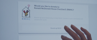 "Shaded background image, close-up of someone at a McDonald's kiosk opting in to ""Round up"" to donate to RMHC"