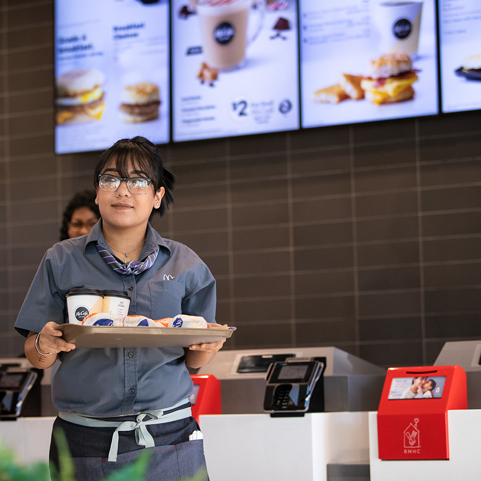 A McDonald's customer carrying their meal on a dine-in tray away from the register, a bright red donation box is featured to the right, breakfast items in soft focus on the menu display