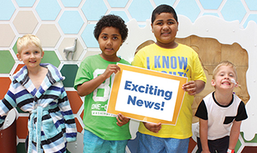 "Article Preview: four children, two in center holding ""Exciting News!"" sign"