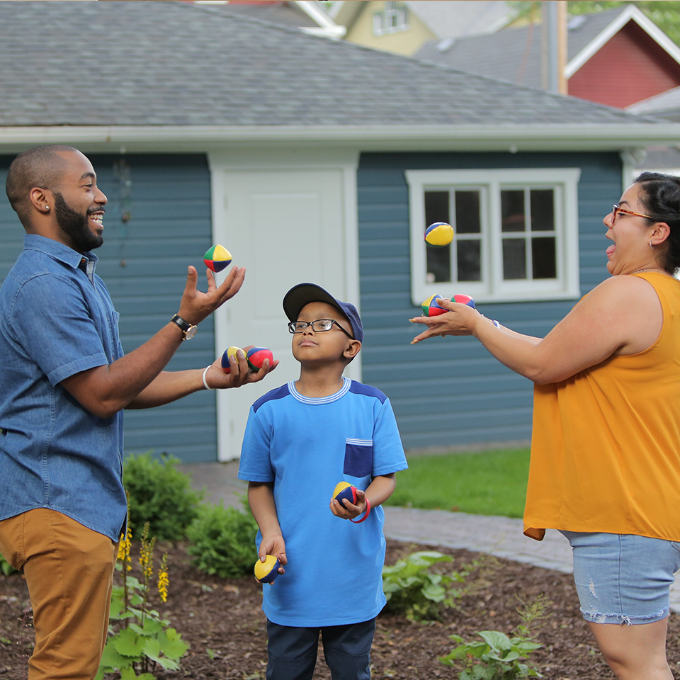 An RMHC family, dad, son, and mom, juggling in their yard, supporting a Raise Love fundraiser