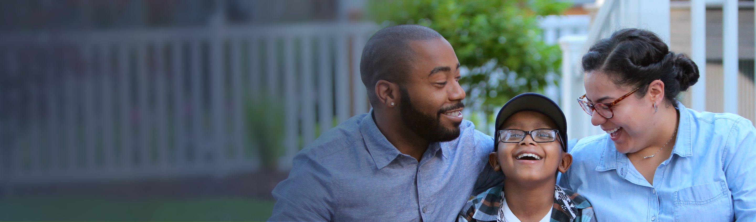 An RMHC family, son between mom and dad, laughing together on their porch, white fence in soft focus in background
