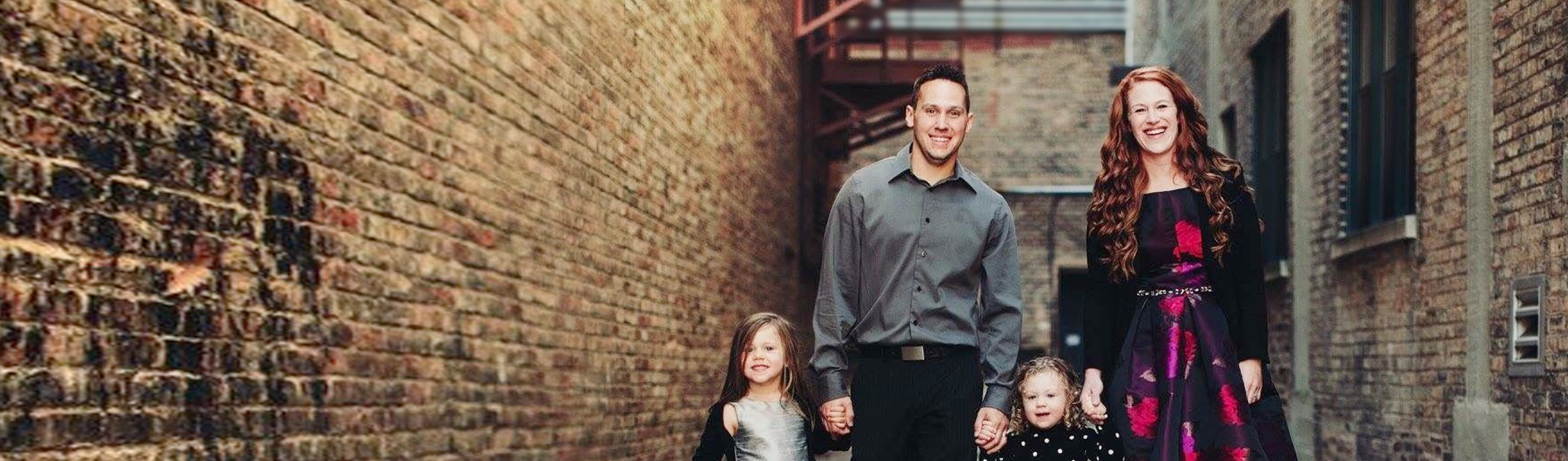 The Ledvinas, an RMHC family, posed holding hands in a picturesque brick-lined alley