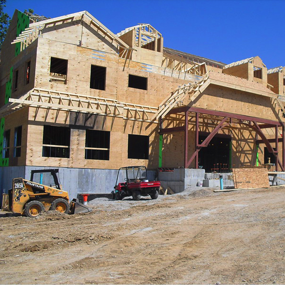 A new Ronald McDonald House program under construction, bare foundation, uncovered plywood walls and frame