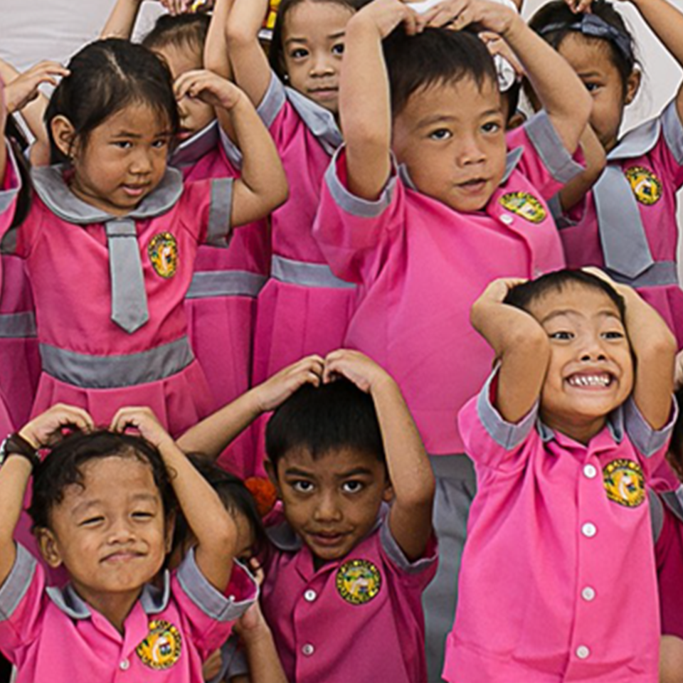 Smiling children at a Bahay Bulilit Learning Center, wearing matching pink school uniforms, all posed with hands on heads