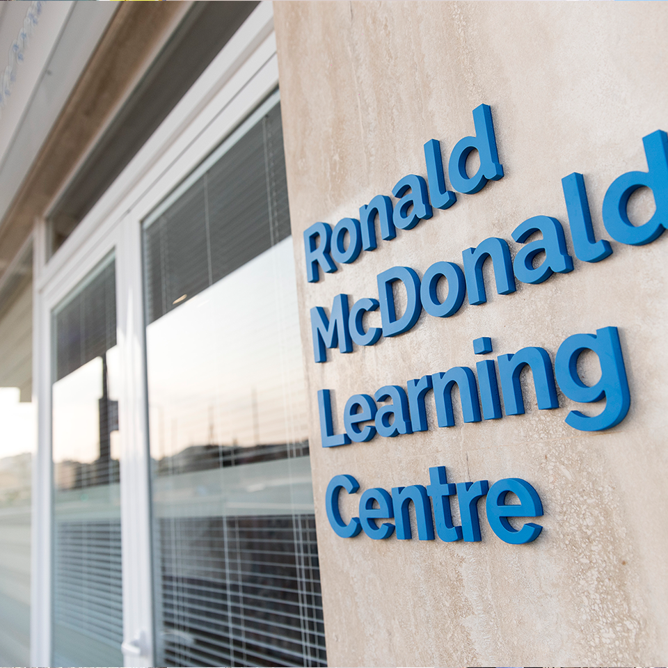 "Building exterior, windows, lettering in blue ""Ronald McDonald Learning Centre"""