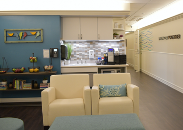 A hospital's Ronald McDonald Family Room common area, two beige armchairs and coffee table in foreground and kitchen, fresh fruit, wall art, and hospital phone in background