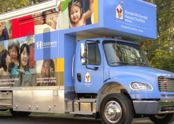 A parked Care Mobile against a background of trees, vehicle wrapped in RMHC family imagery and messaging, RMHC Atlanta