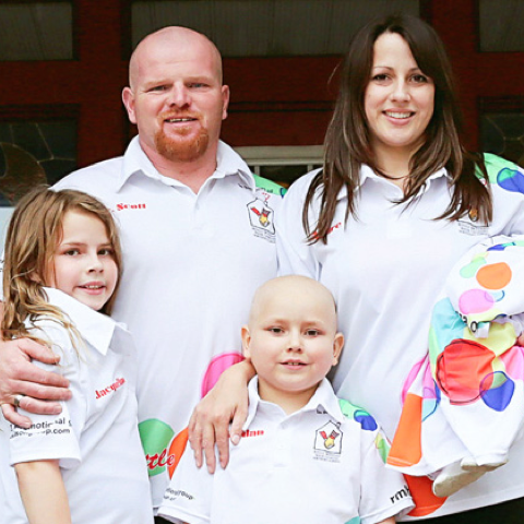 An RMHC family in matching white RMHC polo shirts, dad and mom in back row, children in front