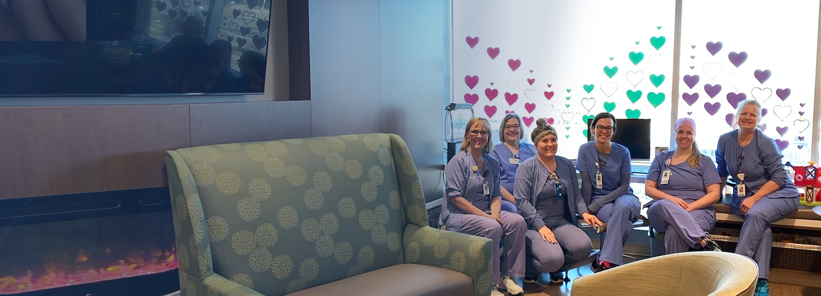 Pediatric nurses sit for the camera, lit by the window behind them decorated with multiple colors of heart symbols, furniture in soft focus in front