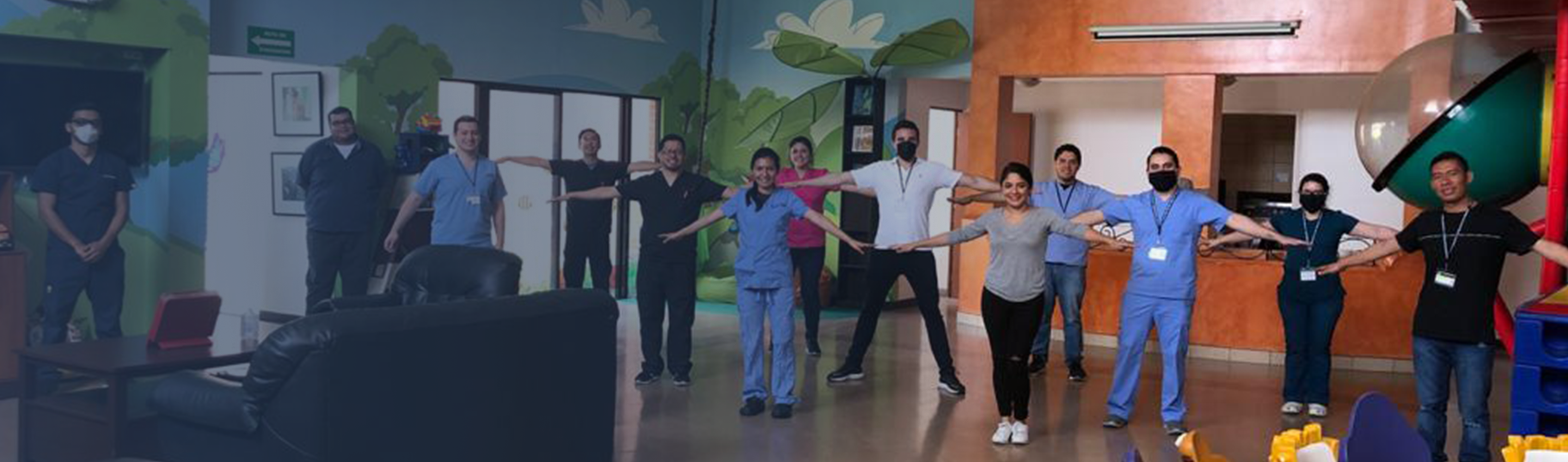 13 healthcare workers and administrators demonstrating social distancing, most wearing face masks and holding arms outstretched to show at least 6 feet of personal space