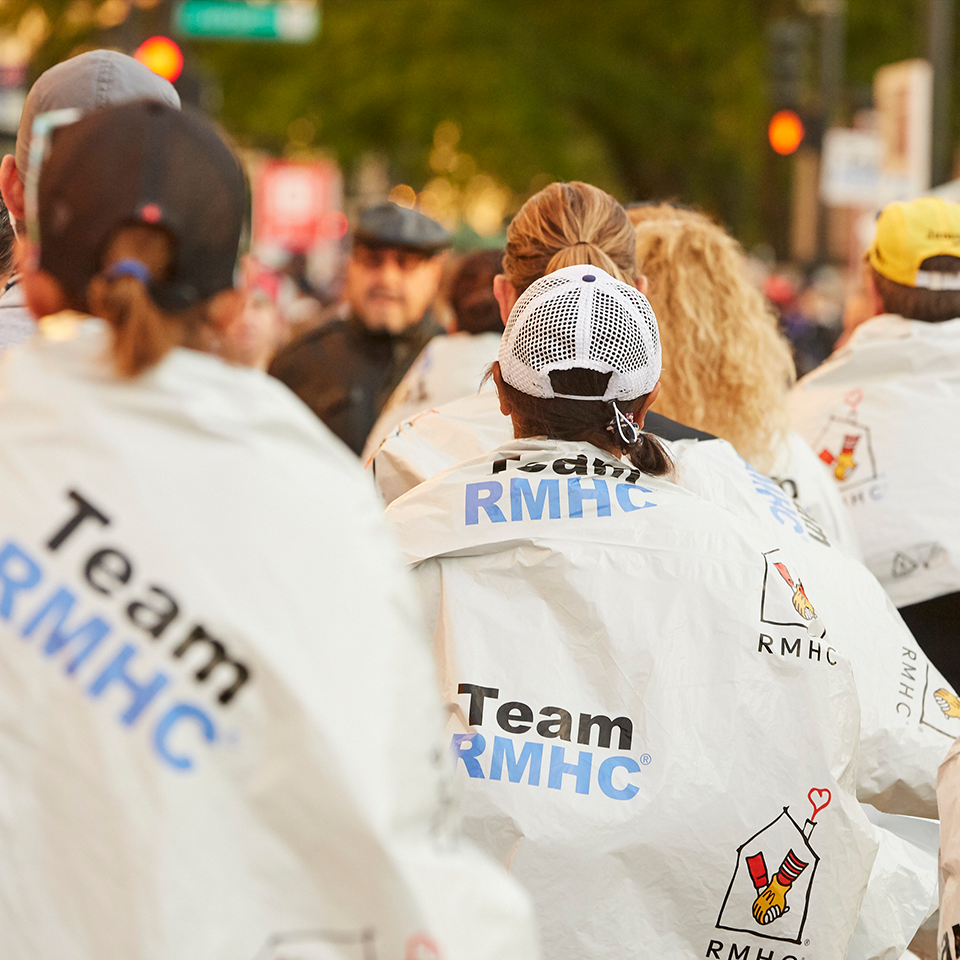 "Team RMHC marathoners in baseball caps, turned away from camera, showing space blankets branded with ""Team RMHC"" and the RMHC logo"