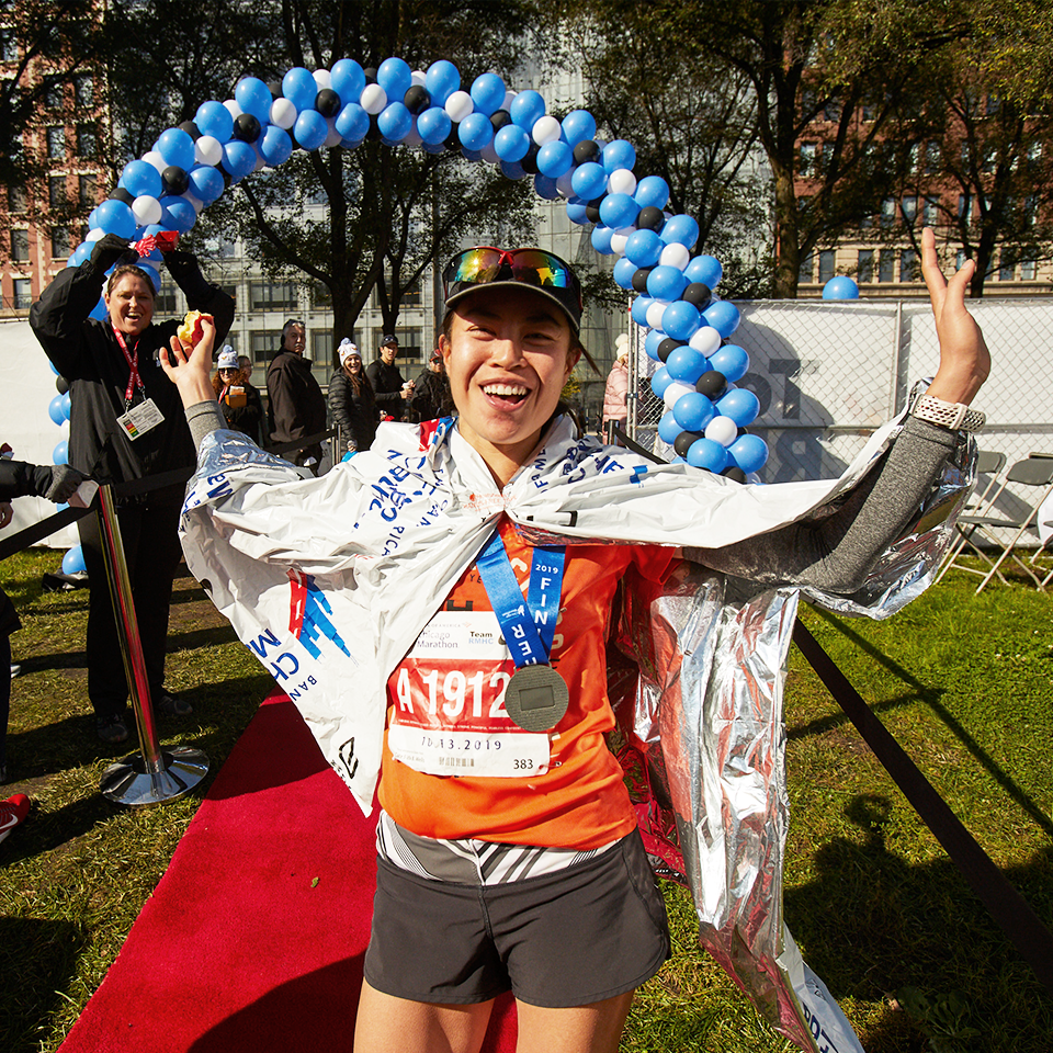 A Team RMHC marathoner after the finish line, wearing a baseball cap, space blanket, bib, and medal